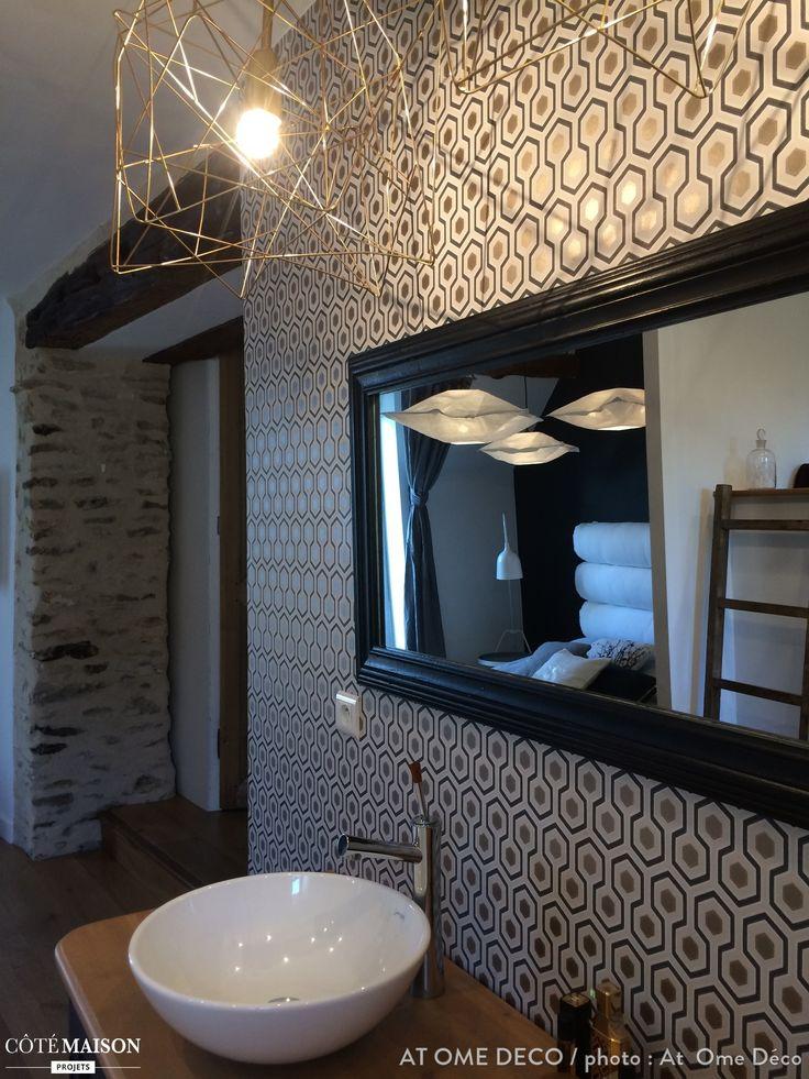 Le coin lavabo d'une salle de bains dont les murs sont habillés de papier peint graphique.