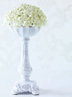 Bouvardia buds and pearl pins form the center of every stephanotis in this floral dome, perched prettily on a glazed terra-cotta candleholder.