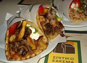 Gyros sandwiches in Greece, with meat, onions, tomato, french fries, and tzatziki sauce rolled into a pita