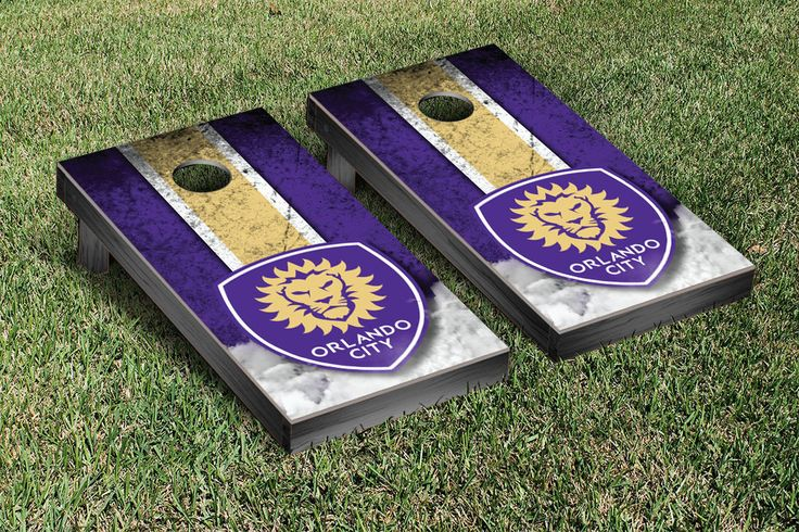 A bean bag toss lawn game complete with a Orlando City Lions style cornhole board, team color duck cloth bags with team logos filled with corn kernels and carrying case for the bags.