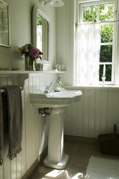 Love the pedestal sink, wainscoting with a shelf