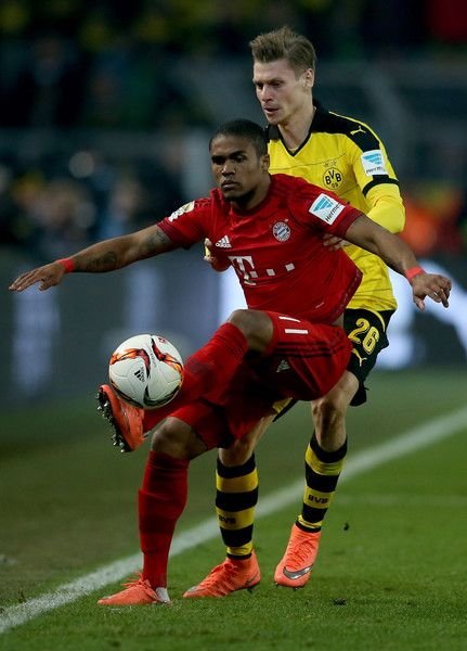 Lukasz Piszczek of Borussia Dortmund and Douglas Costa of Bayern Munich compete for the ball during the Bundesliga match between Borussia Dortmund and FC Bayern Muenchen at Signal Iduna Park on March 5, 2016 in Dortmund, Germany.