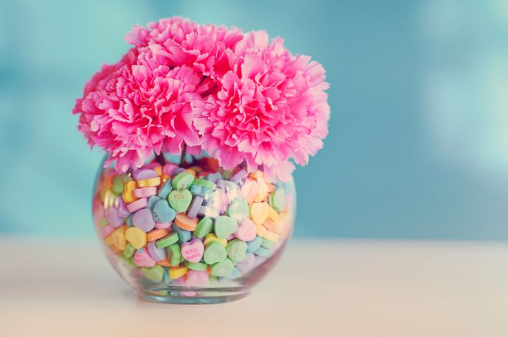 Love this valentine's candy decor using a vase, flowers, and conversation hearts! Too cute!