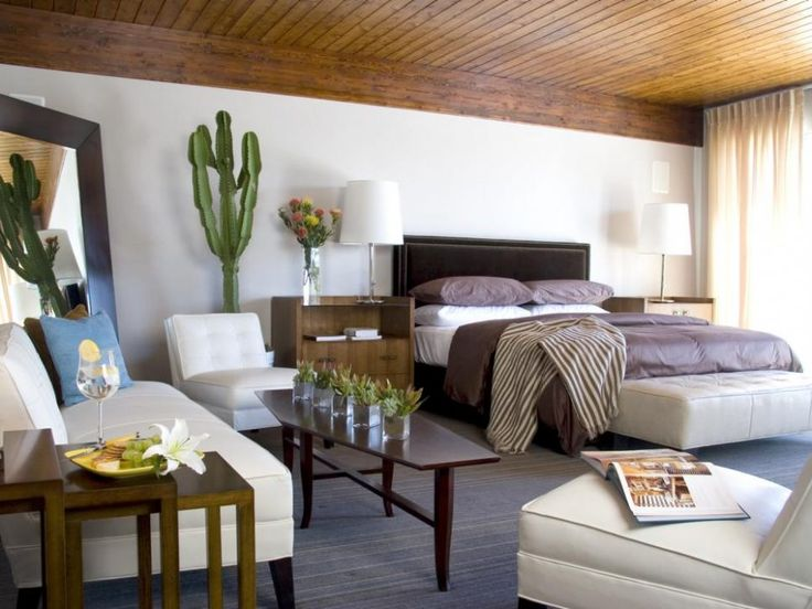 Bedroom: Minimalist Bedroom With Southwestern Flair. minimalist bedroom. wooden ceiling. large bedroom. wooden nightstand. tufted bench. white sofa. stacked accent table. wood framed mirror. wooden table. wood flooring.
