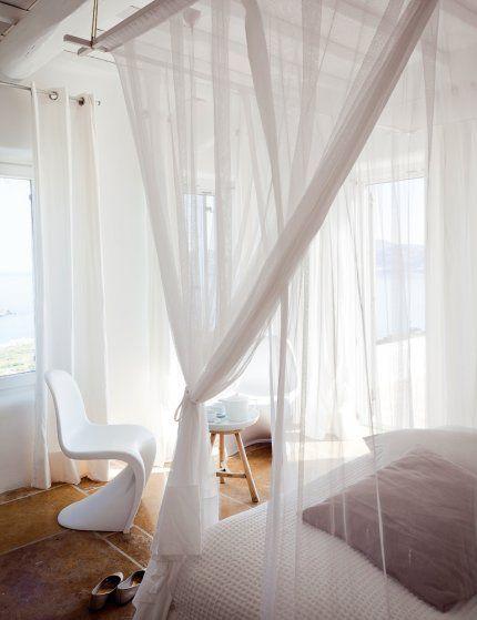 Farniente au lit    Chaque chambre est également équipée de grandes moustiquaires qui viennent tout droit d'Afrique du Sud par une entreprise familiale, Kiwinet. Devant la fenêtre qui laisse filtrer la lumière du matin, la Panton Chair de Knoll.