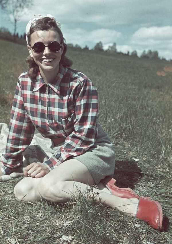 1941. Kvinna i rutig skjorta, shorts, solglasögon och träskor sitter i gräset. color found photo girl in shorts plaid top hillside red shoes 40s war era