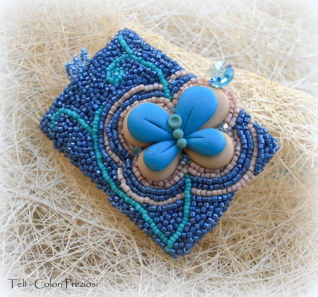 Butterfly in the sky: DIY bead embroidery pendant. A very detailed polymer clay butterfly is surrounded by a design made with turquoise delicas beads.