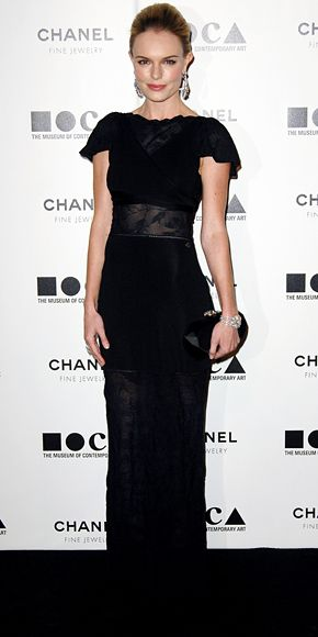 Kate Bosworth wearing a lace-trimmed black Chanel gown with a structured clutch and diamond accessories.