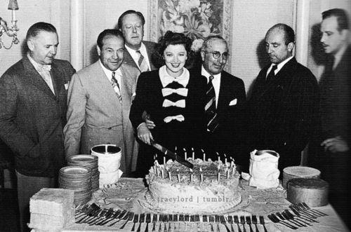 "Celebrating Myrna Loy's thirty-fifth birthday on the set of ""Third Finger, Left Hand"": (second left to right): studio manager Eddie Mannix, her director Robert Z. Leonard, Myrna, Louis B. Mayer, her husband Arthur Hornblow, Jr., and her co-star Melvyn Douglas"