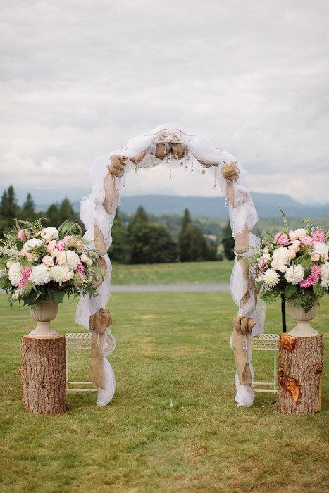 rustic tree stump and flowers wedding arch