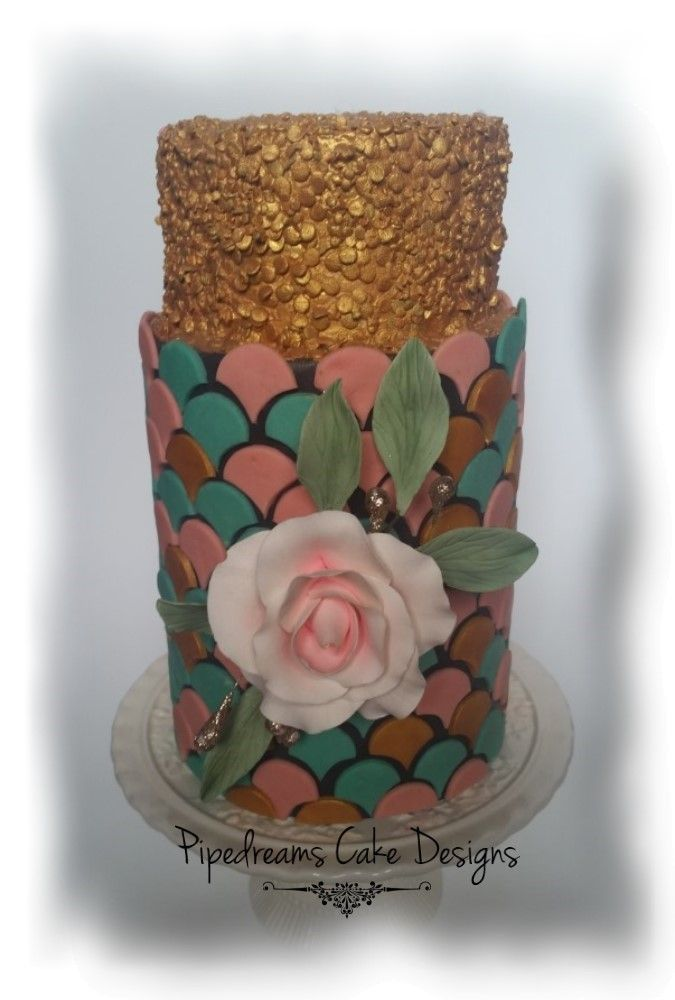 Scallops and sequins cake. Mint, pale pink and gold scallops with a charcoal background on a double barrel tier, topped with a smaller tier of shimmering gold sequins. Finished off with a soft pink rose in the center.