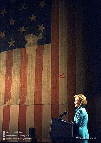 A great photo of Hillary Clinton speaking with an American flag draped in the background