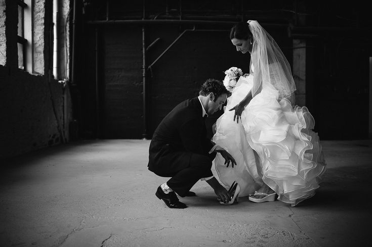groom helping bride with shoe