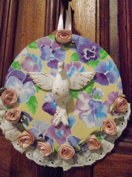Mandala média do Divino, trabalhada com tecido de algodão, florezinhas, renda e fita  Divino em resina trabalhado em pátina provençal  Peça única  Diâmetro: 12 cm R$ 25,00