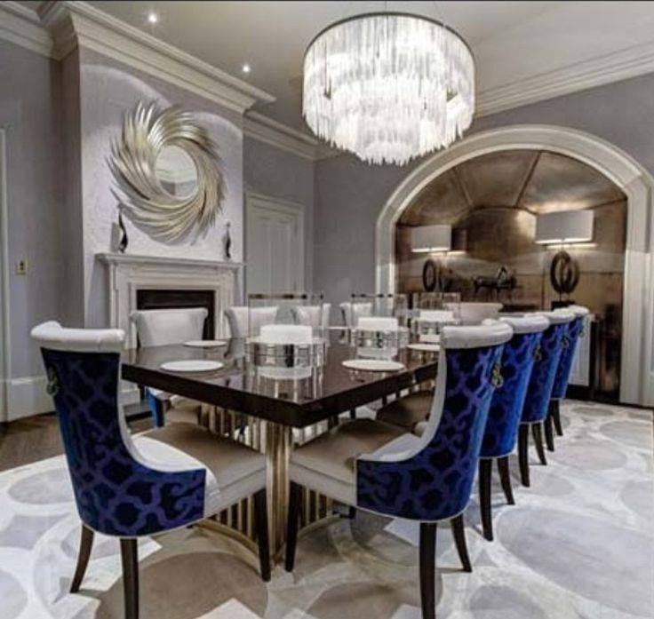 Modern elements, upholstered seating, neutral palette, accent seating, chandelier lighting, mirrored panels, modern furnishings, patterned rug, navy blue accents