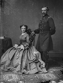 George Armstrong Custer stands behind his wife Libbie.