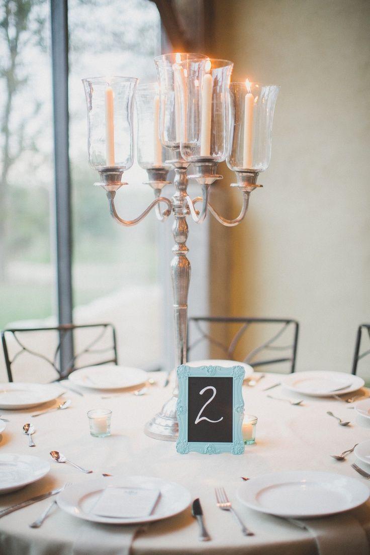 Die hohen Mittelstücke sind hohe silberne Kandelaber mit sich verjüngender Kerze.   – Tischdekoration Hochzeit