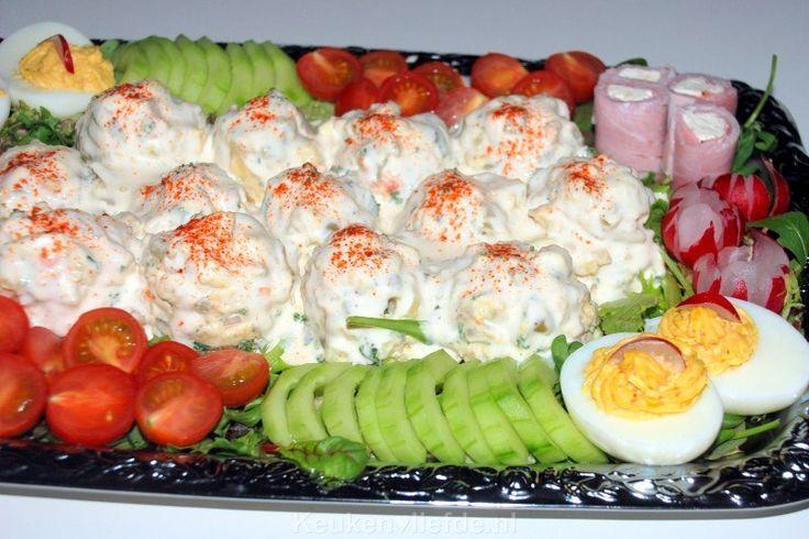 Rijkelijk opgemaakte huzarensalade  1 kilo vastkokende aardappels 4 el azijn Blikje macedoine groenten 2 el kleine zilveruitjes, grof gehakt 5 augurken, fijngesneden 1/2 bosje peterselie, gewassen en fijngehakt 1/2 appel, in kleine blokjes gesneden 3 hardgekookte eieren, fijngehakt 1 sjalotje, fijngesnipperd 3 el mayonaise 3 el crème fraîche Paar druppels maggi Zout en peper