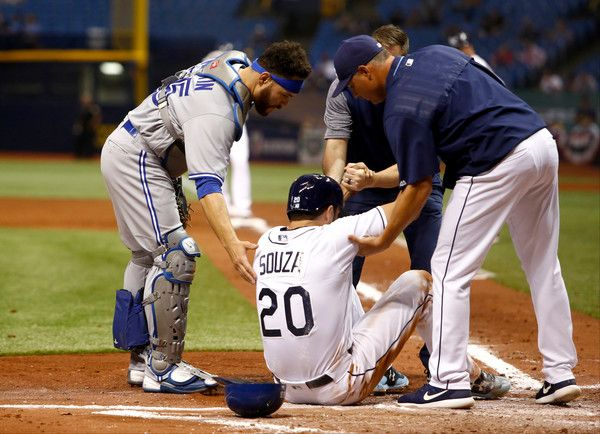 Steven Souza Jr. #20 of the Tampa Bay Rays is helped to his feet by catcher Russell Martin #55 of the Toronto Blue Jays and Rays' manager Kevin Cash #16 after being tagged out at home plate by Martin while attempting to score off of a fielder's choice by Tim Beckham during the fifth inning of a game on April 6, 2017 at Tropicana Field in St. Petersburg, Florida.