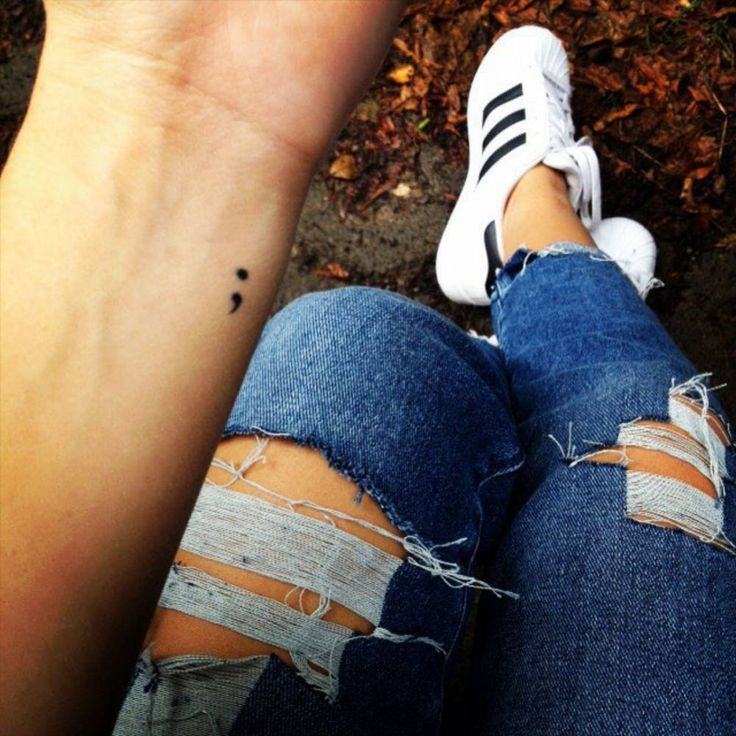 Tatuaje de un punto y una coma en el interior de la muñeca derecha de Selina.