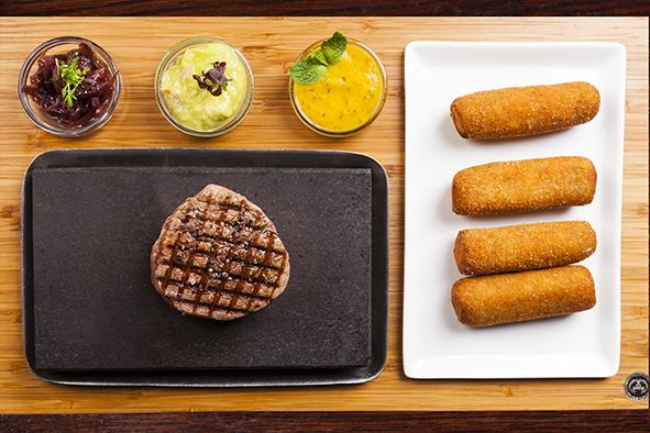 Brazilian tenderloin steak fillet cooked on lava stone, with homemade croquettes of cassava potato