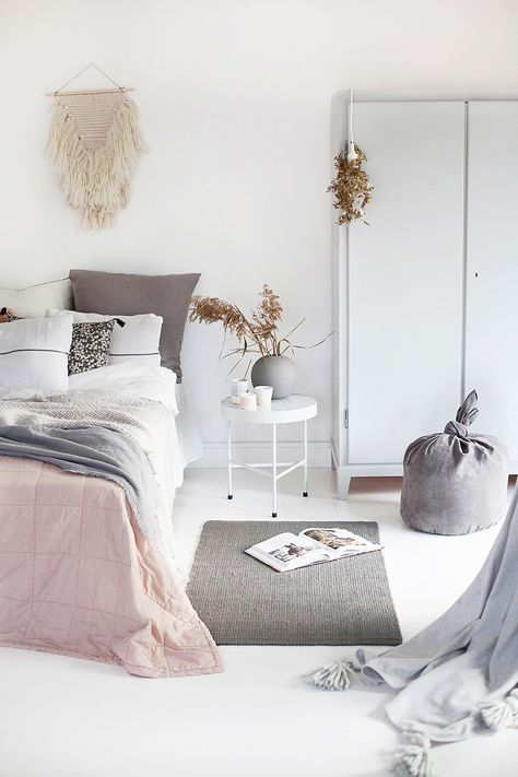 Norwegian Bedroom design - white walls and floor, muted pink bedspread/blanket, and light gray accents (pillows, knit stool) | Interior Design Pro