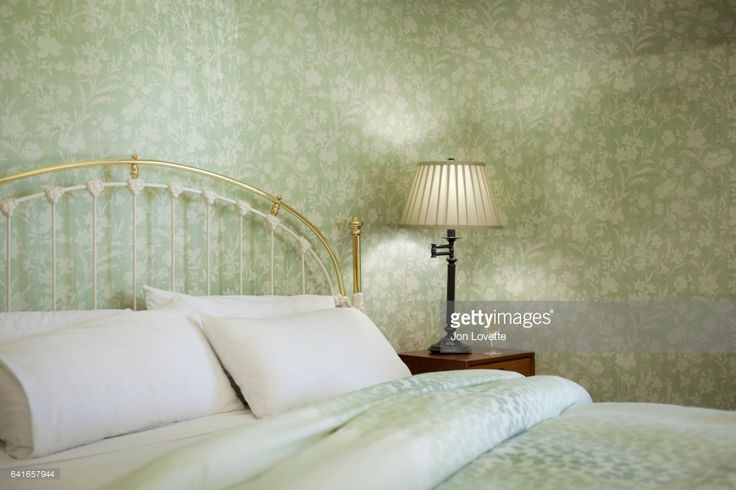 Stock Photo : Pale Green Bedroom with wallpaper and lamp and unmade bed