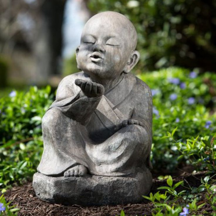Garden statue of young Buddha blowing a wish.