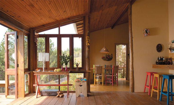 Na sala de estar, as várias madeiras usadas ficam à vista. A estrutura principal é de eucalipto roliço tratado em autoclave.Junto às janelas, a mesma espécie aparece serrada. O piso exibe tábuas de pínus lixadas a mão e aparafusadas nasvigas de eucalipto do andar de baixo