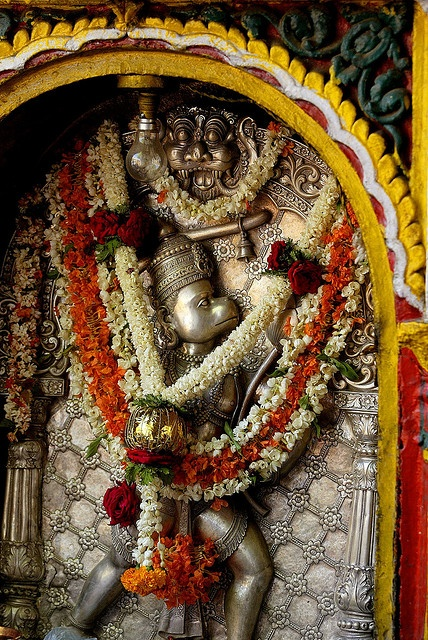 India Hanuman. A flower-laden figure of the Hindu Monkey God Hanuman in the temple Sri Cahmundeswari atop Chamundi Hill in Mysore, India.