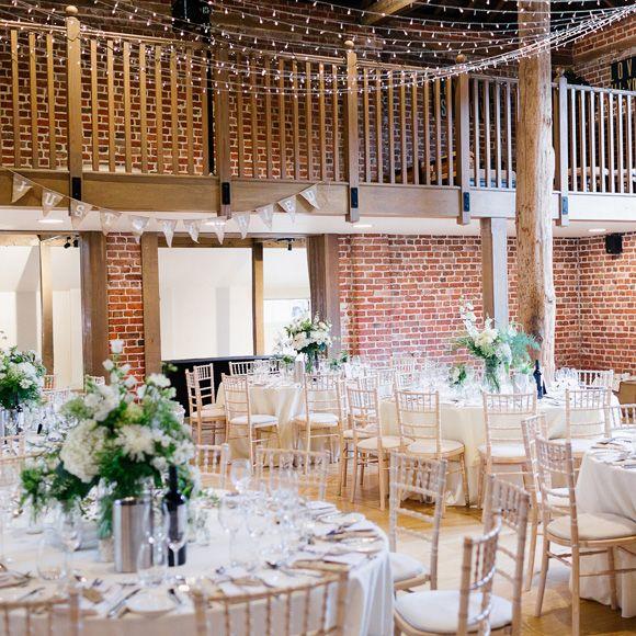 Wedding reception tables set up inside the Mill Barn at Gaynes Park – barn venue hire