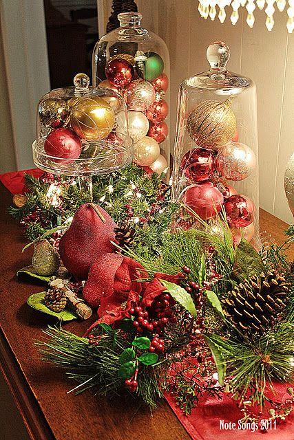 Utiliza stands y tapas de tortas con esferas de navidad para centros de mesa.