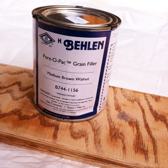 H. Behlen Pore-O-Pac Grain Filler - fills heavy wood grains, so surface is smooth. Just rub on with a rag. Can paint or stain over it.  In the comments section another recommended Brushing Putty by Fine Paints of Europe