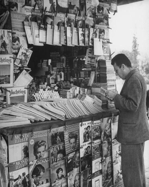 Man looking through magazine at a newsstand on University Street.Location:Athens, Greece Date taken:1948 Photographer:Dmitri Kessel