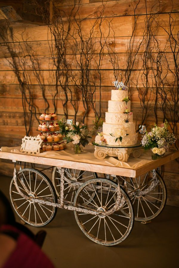 A rustic wedding cake table made with wagon wheels and a branches backdrop, with buttercream cake and strawberry cupcakes.