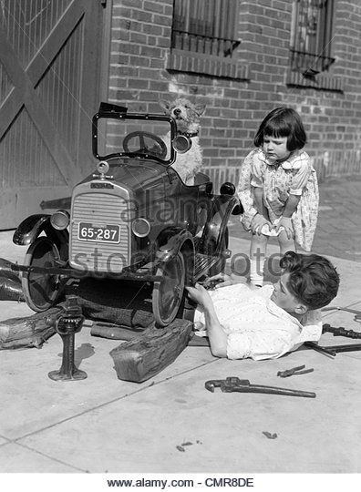 1920s LITTLE GIRL LEANING DOWN WATCHING BOY WORKING UNDER TOY CAR WITH DOG BEHIND WHEEL - Stock Image