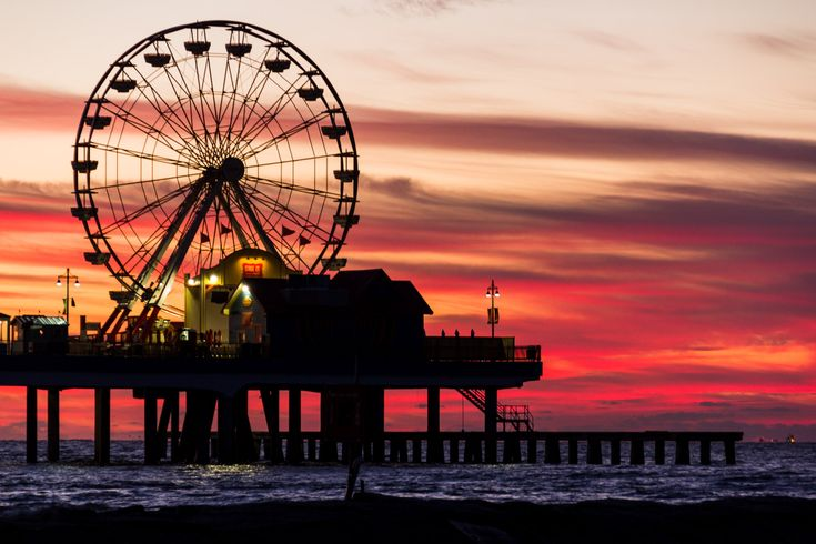 The light of the rising sun silhouettes the Historic Galveston Pleasure Pier as day breaks over the Gulf of Mexico.  See more #photos at 75central.com