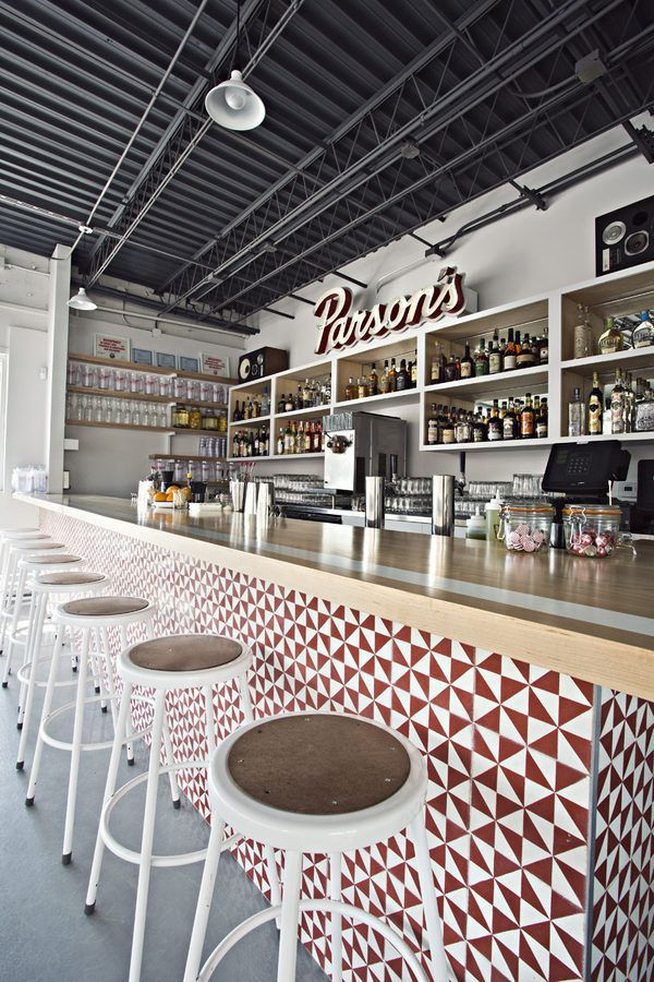 geometric red and white printed tile bar face the stools are wire framed with a wooden seat.