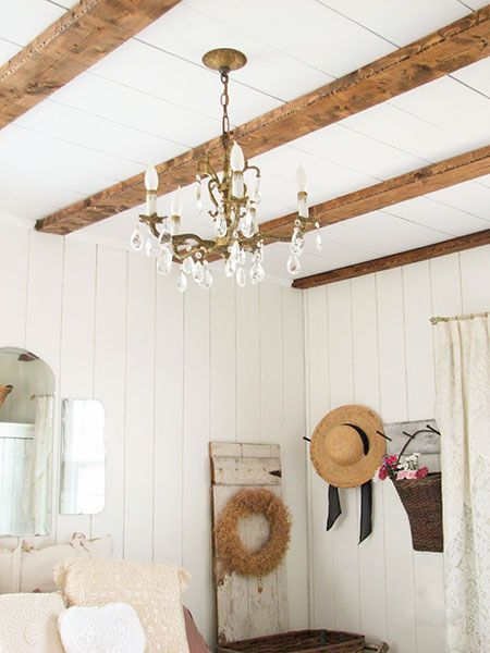 exposed, distressed, pine-wood beams run across the ceiling of this master bedroom with white pine walls and a chandelier