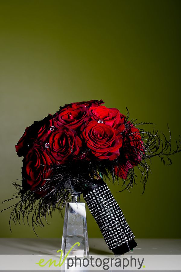 bold red roses and black ostrich feathers in a wedding bouquet