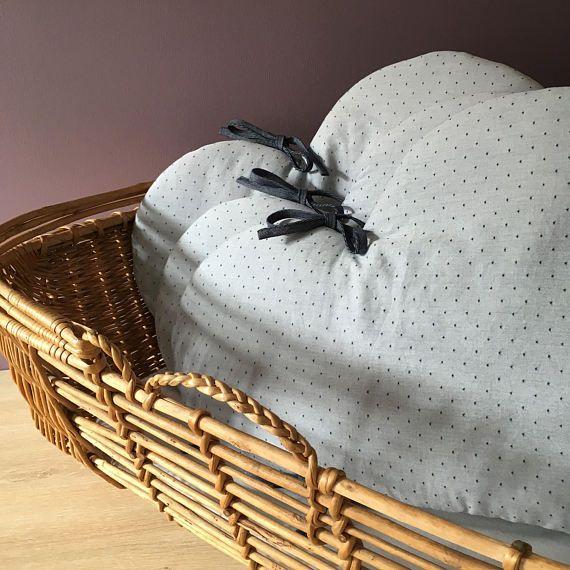 Pour protéger au mieux la tête de bébé, ce tour de lit en forme de nuages a été spécialement conçu pour les lits évolutifs (70*140cm).  Les nuages font environ 70cm de large par 38cm de haut. Ils possèdent chacun 4 liens doubles de 30cm pour les attacher solidement aux barreaux du berceau ou du lit. Ils sont réversibles : un côté en chambray à pois bleu, un côté en double gaze de coton à rayures. A vous de choisir le côté en fonction de vos envies ou du linge de lit de bébé !  Recto en…