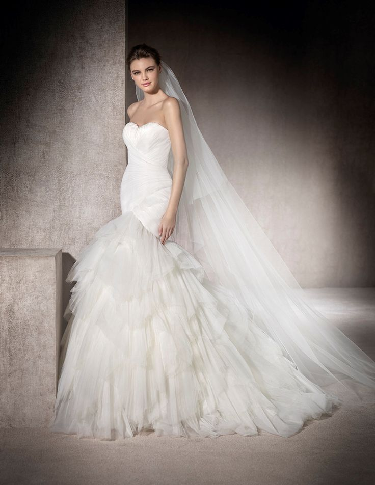 MELOSA - Mermaid wedding dress in draped tulle. The design fits the body with a sweetheart neckline decorated with feathers