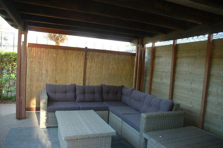 Een strak afdak, dat ruimte biedt voor een grote loungehoek. Aan de achterkant is hij dichtgemaakt met planken, aan de zijkant met rietmatten.