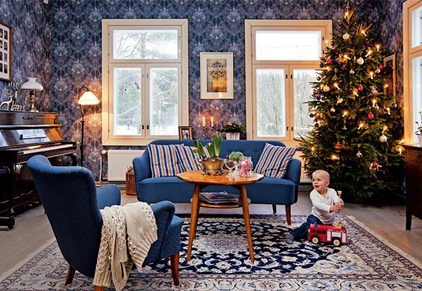 Uudelleen verhoiltu tummansininen sohvakalusto on 1950-luvulta. Sohvapöytä on Portsan katumarkkinoilta. Seinä on tapetoitu Pihlgren & Ritolan William Morris -tapetilla. | KUUSI KRUUNAA PUNAISEN TALON JUHLAN | Koti ja keittiö