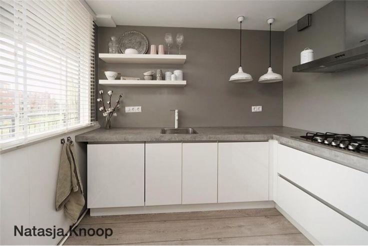 Wit gecombineerd met betonnen keukenblad, grijze muur en houten vloer