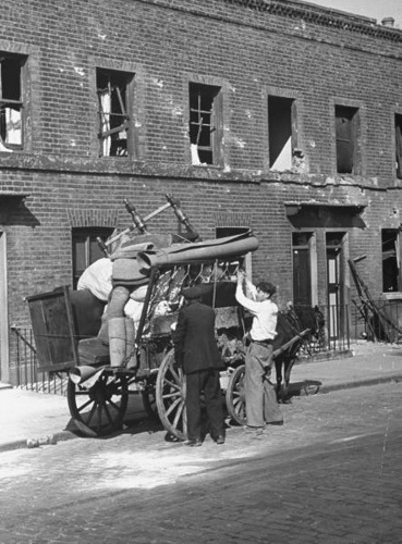 1940 London at War - East End London 1940 - Ramlay family load a horse drawn cart with furniture while moving from their bombed out East End home, destroyed during a German air raid attack on the city.