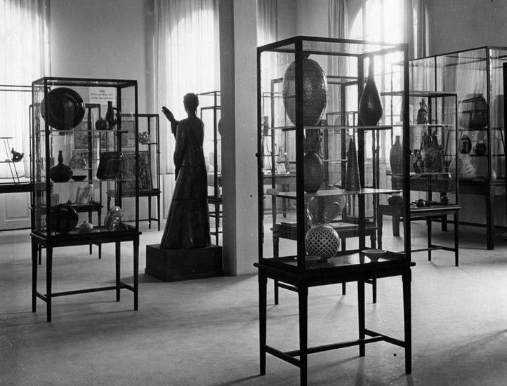 """Scorcio di una sala in una foto del 4 novembre 1949; in primo piano le vetrine con i """"Bianchi di Faenza"""""""