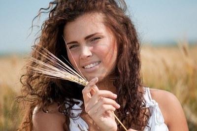 Bella donna con perfetto capelli e pelle posing in campo di grano sulla giornata di sole estivo. Picnic. Archivio Fotografico