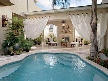 """potted foliage adds greenery to pool area, the not so standard outdoor curtain & pair of chaise lounges beside the fireplace...adds plenty of extra """"living"""" space"""