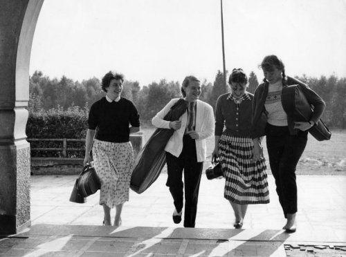 Jongeren. Vier meisjes met vlechtjes, paardestaarten, wijde rokken en vestjes, lopen met een muziekinstrument onder hun arm de trap van een gebouw op. Plaats onbekend. 30 nov. 1957.